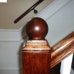Stained Red Oak wooden balls on a staircase banister with yellow wainscoting
