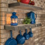 Light stained floating shelf on brick wall